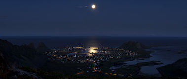 Arctic midnight cityscape- Vaeroy island. Midnight panorama with the moon above the town of Vaeroy, Lofoten islands, Norway Royalty Free Stock Image