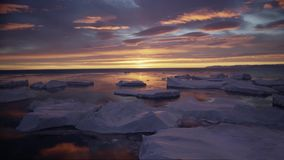 Arctic landscape with icebergs in Greenland icefjord with midnight sun sunset / sunrise in the horizon. Aerial drone stock video