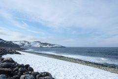 Arctic ocean background with snowy coast in. View of clear sky , dark blue sea , black stone , and white snow mountain along the coast of the Arctic Ocean in royalty free stock photography