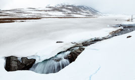 Arctic river falling into a hole in snow stock photo