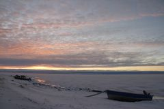 Arctic sunrise with a boat in the foreground. Near Cambridge Bay Nunavut Canada Stock Image