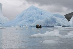 Arctic tourism. Tourists sailing next to an iceberg in the high arctic (Greenland Royalty Free Stock Photography