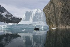 Arctic tourism. Tourists sailing next to an iceberg in the high arctic (Greenland Royalty Free Stock Photos