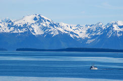 Arctic wilderness. Snow capped mountain range towers over commercial fishing boat in the foreground Stock Image