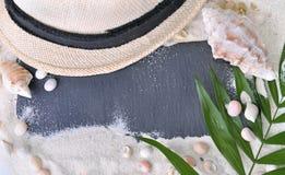 ardósia na areia com chapéu e escudos foto de stock royalty free