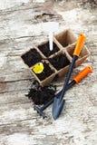 Arden utiliza ferramentas a pá, ancinho, potenciômetros da turfa no fundo de madeira velho Foto de Stock