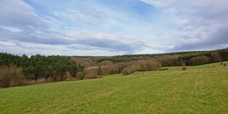 Ardennes landscape with flanks of rolling hills with pine and other trees. Under a blue sky with soft clouds Stock Photography