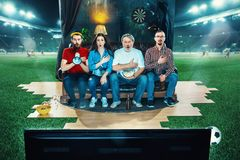 Ardent fans are sitting on the sofa and watching TV in the middle of a football field. royalty free stock image