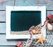 Ardesia in bianco d'annata della scuola con la decorazione marina Fotografie Stock
