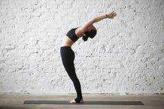 年轻Ardha Chakrasana姿势的,顶楼backg信奉瑜伽者可爱的妇女 免版税库存图片