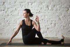 年轻Ardha Matsyendrasana姿势的信奉瑜伽者可爱的妇女,白色 免版税库存照片