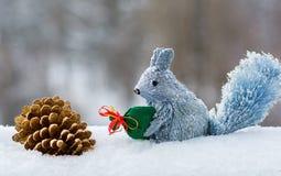 Ardilla decorativa con un bolso de regalos y en cono decorativo del pino en la nieve imagen de archivo