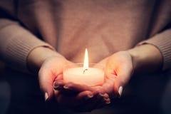 Ardore leggero della candela nel woman& x27; mani di s Pregare, fede, religione Fotografie Stock