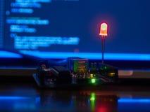 Arduino con el diodo electroluminoso rojo contra una pantalla del cuaderno Fotografía de archivo