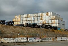 White shipping containers sitting on a grungy hill in Wilmingon. The area adjacent to the Port of Los Angeles is fill with shipping containers, trucks, trailers royalty free stock image