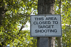 This area Closed to Target Shooting Sign. White and Black this area Closed to Target Shooting Sign on tree with green leaves in the background at Rabbit Slough Royalty Free Stock Image