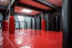 Area d'inscatolamento rossa con i punching ball Fotografia Stock Libera da Diritti