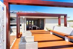 Area di disposizione dei posti a sedere all'aperto del patio di una casa moderna con il pavimento di legno Fotografia Stock