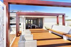 Area di disposizione dei posti a sedere del patio di una casa moderna e di un pavimento di legno Fotografia Stock