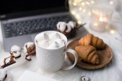 Area di lavoro bianca di blogger accoglienti di inverno con il computer portatile, caffè con la m. fotografie stock