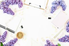 Area di lavoro di blogger con la lavagna per appunti, la latteria, la busta, il lillà e gli accessori su fondo bianco Disposizion Fotografie Stock