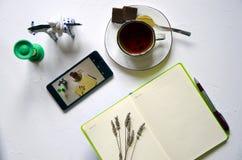 Area di lavoro con il blocco note, tazza di tè su un fondo bianco Disposizione piana, scrittorio di scrittura della scrivania di  immagine stock