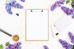 Area di lavoro con la lavagna per appunti, la latteria, la penna, i rami lilla e gli accessori su fondo bianco Disposizione piana Fotografia Stock Libera da Diritti
