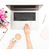 Area di lavoro con le mani femminili, computer portatile, mazzo rosa delle rose, tazza da caffè, diario della donna Vista superio fotografia stock libera da diritti