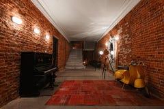 Area di lavoro creativa industriale moderna scala con i mura di mattoni strutturati al sottotetto della soffitta Immagine Stock