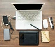 Area di lavoro della Tabella con il computer portatile e l'attrezzatura per sincronizzazione Immagini Stock