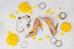 Area di lavoro femminile con gli accessori gialli del ` s delle donne e dei fiori Fotografia Stock