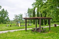 Area di picnic e giochi del ` s dei bambini nel parco in mezzo dell'erba alta Fotografie Stock Libere da Diritti