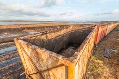 Area estraente della torba con il vecchio carretto vuoto nella priorità alta Fotografia Stock Libera da Diritti