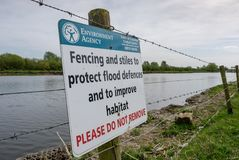 Warning signs by the side of a deep inland river, prone to flooding. royalty free stock images