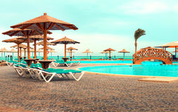 Area hotel with swimming pool with sunbeds and umbrellas royalty free stock images
