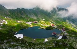 Area of lake Balea in clouds. Gorgeous summer landscape of Fagarasan mountains, Romania. popular tourist location observed from the top of the ridge Stock Photography