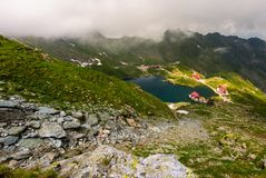 Area of lake Balea in clouds. Gorgeous summer landscape of Fagarasan mountains, Romania. popular tourist location observed from the top of the ridge Stock Photo