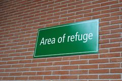 Area of refuge sign on brick wall royalty free stock photography