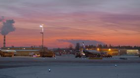 Area of Sheremetyevo Airport with planes and vehicles at the dawn in winter. Moscow, Russia - November 11, 2017: Panning shot of Sheremetyevo Airport at the dawn stock video
