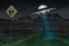 Area 51 Surreal Alien UFO Sighting. Surreal UFO sighting in what may be Area 51. A spaceship flies above the earth with a road sign warning to watch for aliens Stock Photo