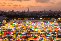 Area view multiple colors weekend market with city downtown background Stock Photos