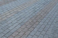 Area or walkway made of granite or marble rectangular tiles grey and brown. Tiles laid out in a line, line by line. Visible streaks in the tiles stock photography