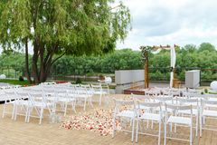 Area of the wedding ceremony near river on the pier. Wooden rect. Angular arch, white chairs decorated with flowers, greenery, petals, eucalyptus and tulle. Cute Royalty Free Stock Photos