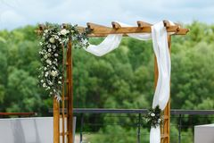 Area of the wedding ceremony near river on the pier. Wooden rect. Angular arch, white chairs decorated with flowers, greenery, petals, eucalyptus and tulle. Cute Stock Photos