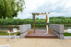 Area of the wedding ceremony near river on the pier. Wooden rect. Angular arch, white chairs decorated with flowers, greenery, petals, eucalyptus and tulle. Cute Royalty Free Stock Images
