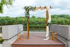 Area of the wedding ceremony near river on the pier. Wooden rect. Angular arch, white chairs decorated with flowers, greenery, petals, eucalyptus and tulle. Cute Stock Photography
