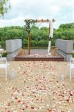 Area of the wedding ceremony near river on the pier. Wooden rect. Angular arch, white chairs decorated with flowers, greenery, petals, eucalyptus and tulle. Cute Royalty Free Stock Photography