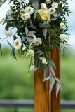 Area of the wedding ceremony near river on the pier. Wooden rect. Angular arch, white chairs decorated with flowers, greenery, petals, eucalyptus and tulle. Cute Stock Images