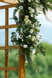 Area of the wedding ceremony near river on the pier. Wooden rect. Angular arch, white chairs decorated with flowers, greenery, petals, eucalyptus and tulle. Cute Royalty Free Stock Photo