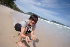 Areia da terra arrendada da mulher na praia Fotografia de Stock